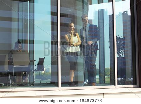 Confident business partners walking down in office building and talking