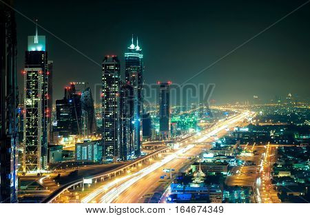 Amazing Night Dubai Downtown Skyline With Tallest Skyscrapers And Road Leading To Abu Dhabi During R
