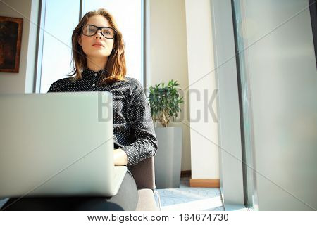Hipster Girl use Laptop huge Loft Studio.Student Researching Process Work.Young Business Woman Working Creative Startup modern Office.Analyze market stock, new strategy. Horizontal