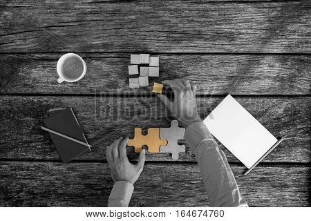Overhead view of hands of businessman solving puzzles at work on desk next to coffee cup and notepad greyscale image with selective colour.