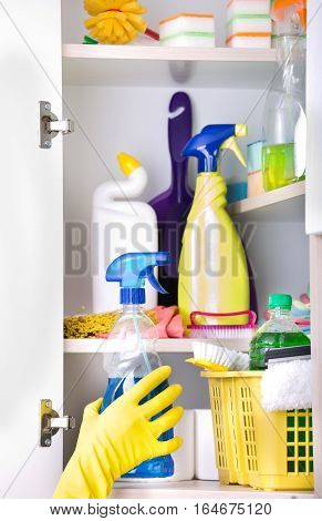 Woman Putting Spray Bottle In Pantry