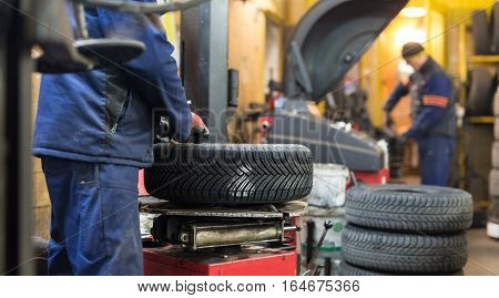 Professional auto mechanic replacing tire on wheel in car repair workshop.