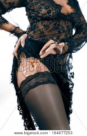 Female hands in black lace gloves hold heart shaped gingerbread cookie with red ribbon tuck into stocking body in black transparent lace dress incognito close up. Valentine's day and love concept