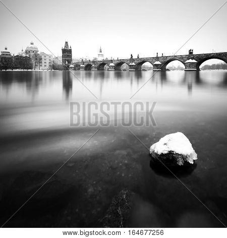 Charles bridge during winter time with frozen river Prague Czech republic