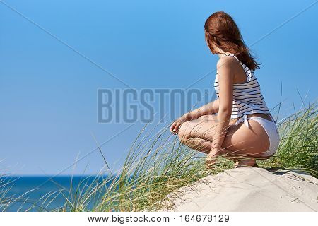 Young woman sitting in the sand dunes and looking at the sea