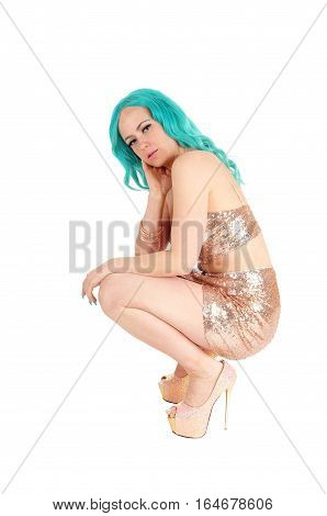 A beautiful woman in a gold colored skirt and top with long blue hair crouching in profile on the floor isolated for white background.