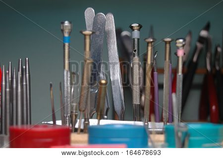 Bunch of various precise hand tools arranged in a row macro shot with a shallow depth of field