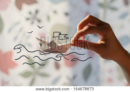 Paper boat in hand. Painted sea with waves and seagulls