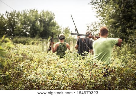 Hunting scene with hunters breakthrough thickets during hunting season in hot summer day