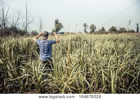 Hunter boy breaks through tall grass during hunting season in summer day with copy space
