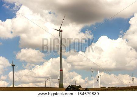 Windmills on the field. Wind generators turbines generating electricity summer landscape. Green Renewable Energy.