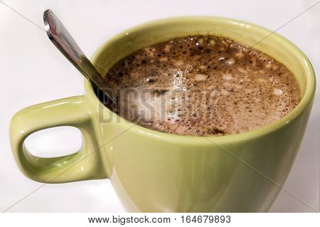 Green cup of coffee cappucino with foam on a white background. Isolated with clipping path.