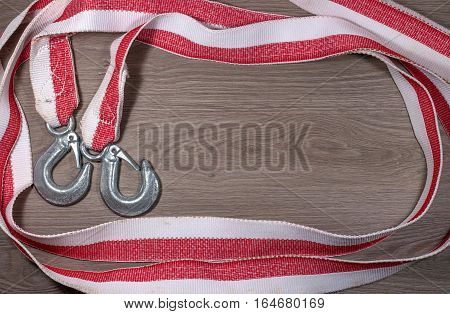 Tow rope for a car on wood background. Rope folded photograph perimeter, two hooks on the left.
