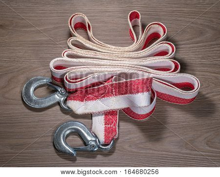 Tow rope for a car on wood background. Cable elegantly assembled in the center of the photo.