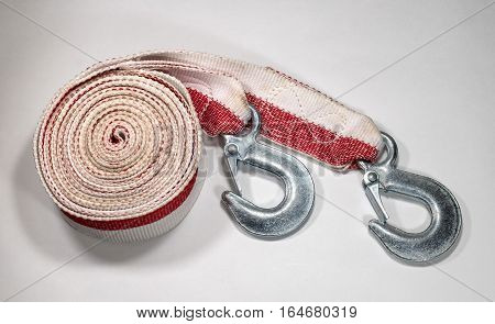 Tow rope to the car on a light background. Rope folded in circle hooks are nearby.