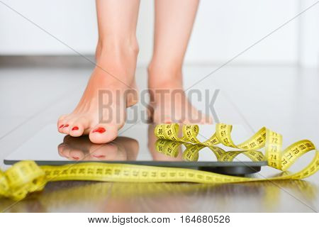 Woman stepping on a weight scale surrounded by yellow measuring tape suggesting diet or weight issues