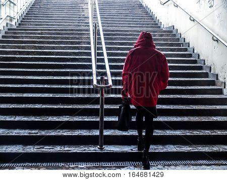 Bucharest Romania 27 February 2016: A woman dressed in a red raincoat is walking up the stairs in Piata Romana metro station in Bucharest.