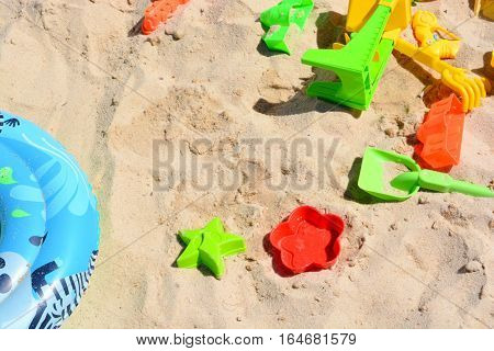 Many colorful beach toys in sand suggesting summer holiday