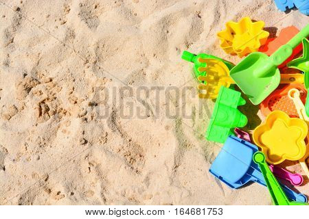 Many colorful beach toys laying on the sand