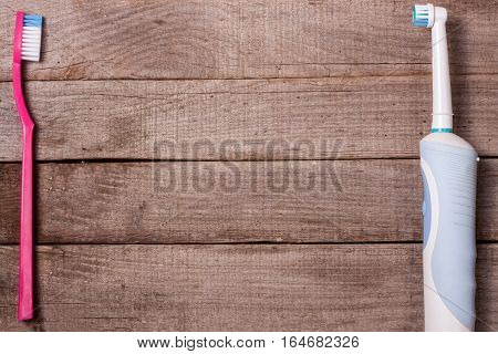 electric and manual toothbrushes on the wooden background.