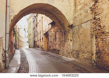Narrow street and old arch. Aged walls of bricks. Tour to the past.