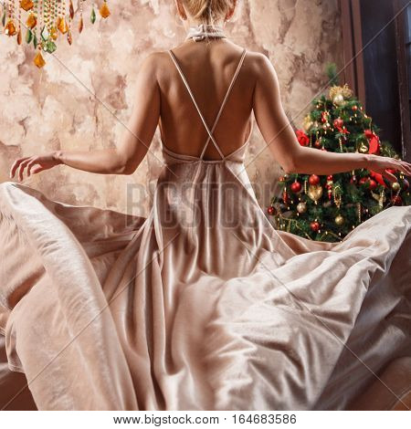 Beautiful sexy blonde in dress posing in a castle by the Christmas tree and piano