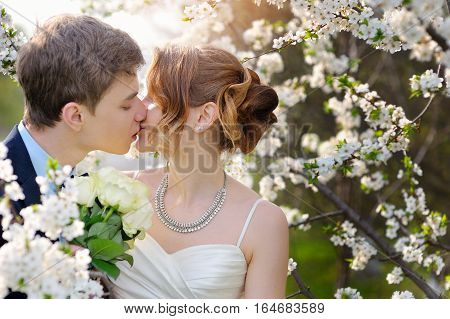 bride and groom at the wedding kiss in spring walk Park.