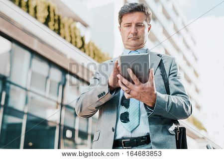 Close up portrait of a successful businessman using a digital tablet while standing by a modern office building.