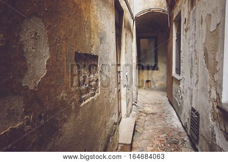 Narrow path between buildings. Old damaged walls. Secrets around every corner.