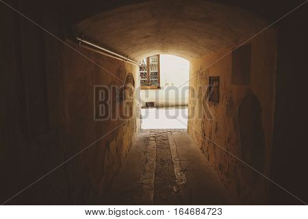 Small dark tunnel. Aged walls with cracked paint. Way to the light.