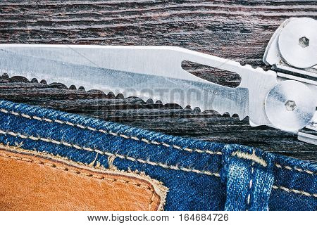 Blue jeans stitched edge and utility multifunctional knife on dark wood. Macro view