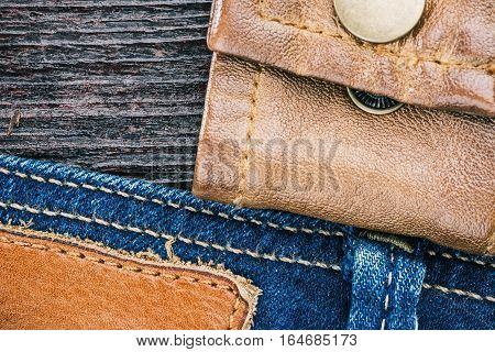 Blue jeans stitched edge, leather jacket cuff and dark brown wood combined background. Macro view