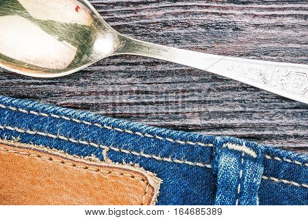 Blue jeans stitched edge and teaspoon on wood background. Macro view
