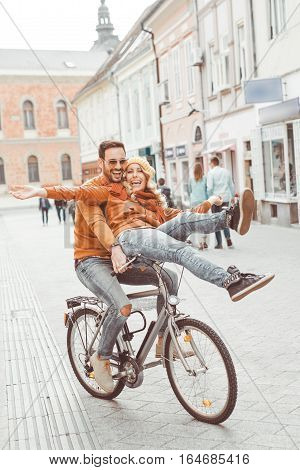 Couple in love in autumn.Happy young couple going for a bike ride on a autumn day in the city.They are having fun together.