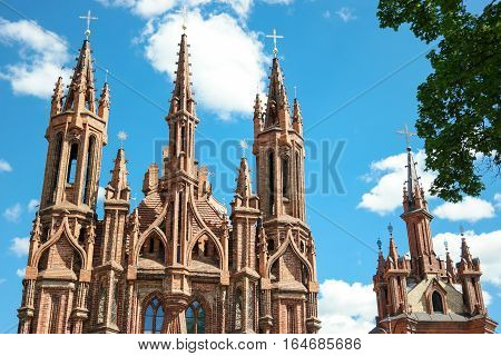 Church on sky background. Towers of cathedral with crosses. Beauty of gothic architecture.