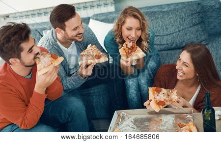 Friends eating pizza.They are having party at home eating pizza and having fun.