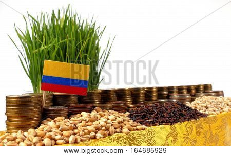 Colombia Flag Waving With Stack Of Money Coins And Piles Of Wheat And Rice Seeds