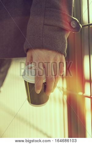 Detail of a man's hand holding a cup of take away coffee outdoors in the daylight