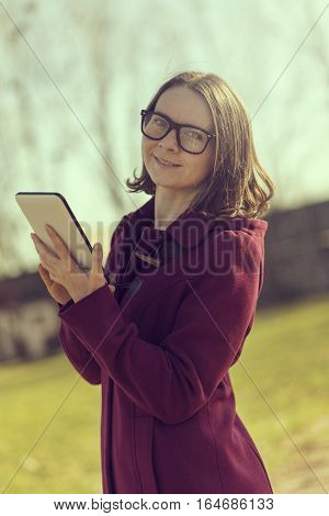 Girl in a park surfing the internet on a tablet computer