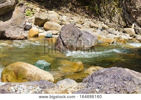 Colorful stones in the mountain river Bogunia: jade, porphyry, and others. Russia, Krasnodar region, Mostovskoy district