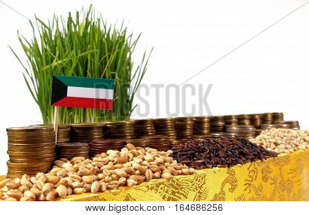 Kuwait Flag Waving With Stack Of Money Coins And Piles Of Wheat And Rice Seeds