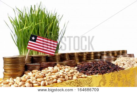 Liberia Flag Waving With Stack Of Money Coins And Piles Of Wheat And Rice Seeds