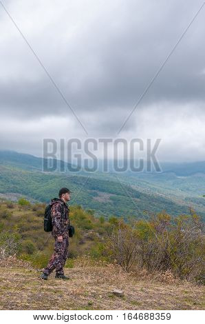 Hill walker in camouflage standing in the middle of mountain wilderness in his autumn travel around Crimea