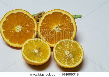 Healty food with spoon of cereals. Orange and lemon are next to cut in half ready to wringing -squeezing isolated on white background.