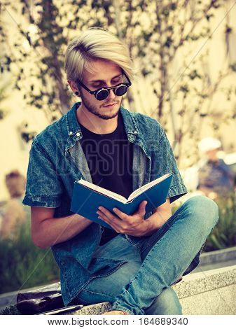 Male fashion student concept. Guy holding and studying from notebook wearing jeans outfit and eccentric sunglasses sitting on white ledge