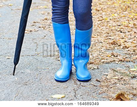 Girl with blue rubber boots and umbrella