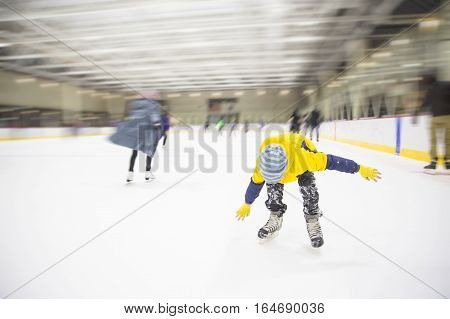 child falling down on the ice rink. the boy lost his balance on skates. blurred background due to the concept. empty space for your text