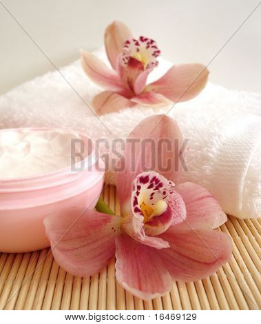 Spa essentials (cream, white towel and pink orchids)