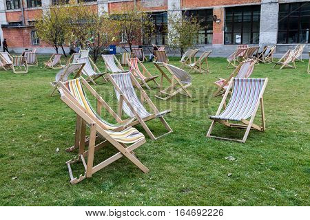 Sunbeds on the green lawn. Summer chair. Many summer chairs outside.