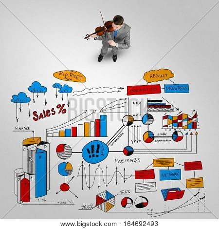 Top view of businessman playing violin and plan sketches on floor
